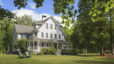 Victorian farmhouse home with lawn and large front porch in summer, Maple Leaf Inn, Barnard,Vermont, USA