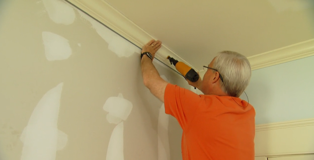 Use a nail gun to install the crown molding.   Today's Homeowner with Danny Lipford