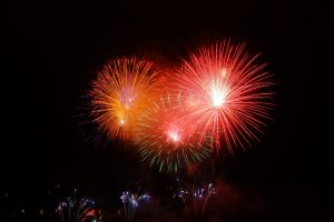 red and orange fireworks against a black sky