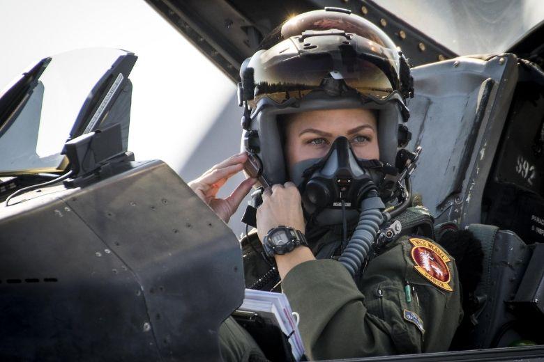 Air Force pilot buckling helmet.