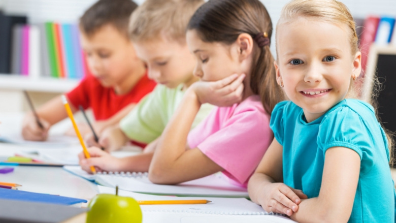 Young children at a table with notebooks and pencils.
