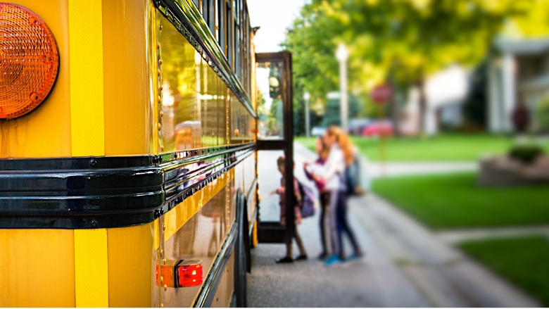 Students getting into a school bus.