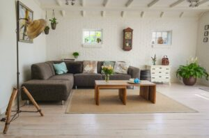 A modern living room with a l-shaped couch, bird pillows, and minimal antique decor