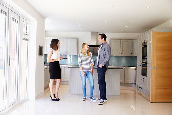 Real Estate Agent Showing a Home to a Happy Couple