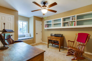 Guest bedroom with window seat and built-in bookshelves