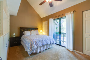 Guest bedroom with balcony and built-in shelving