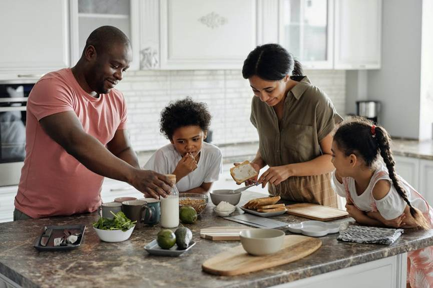 A happy family gathered around a kitchen island, preparing breakfast together.