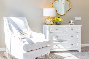 Bright white modern rocking chair in nursery room with chest of drawers decorations in model staging home apartment or house