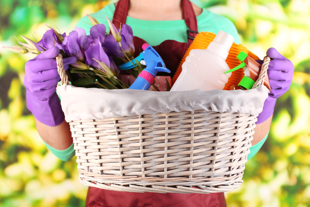 Woman holding basket with cleaning equipment on bright background. Conceptual photo of spring cleaning.