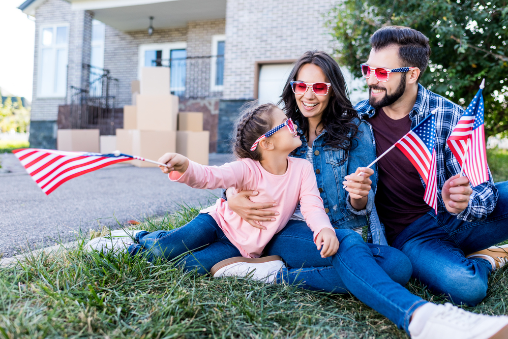 Family sitting in yard with flags, moving into new home.