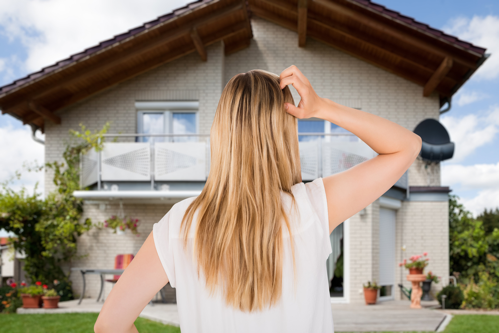 Woman scratching her head looking at a home.
