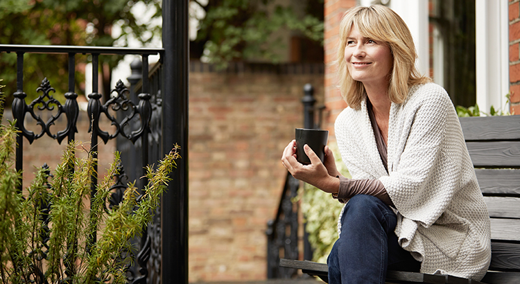 Shot of a mature woman sitting on a bench on her front porch drinking a coffee