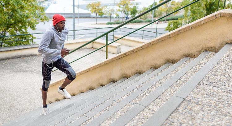 Full Length On Man Jogging On Steps In City