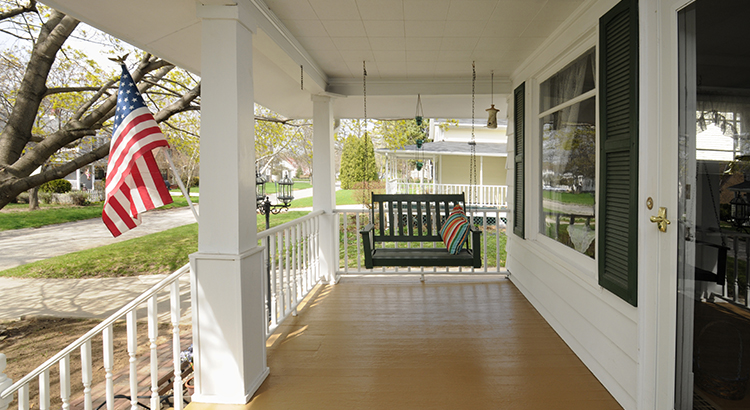 This is a traditional wooden front porch with swinging seat and white pillars. An American flag is displayed in the front yard.