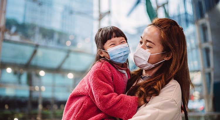 Pretty young mom in medical face mask talking joyfully with her lovely daughter while holding her in train station