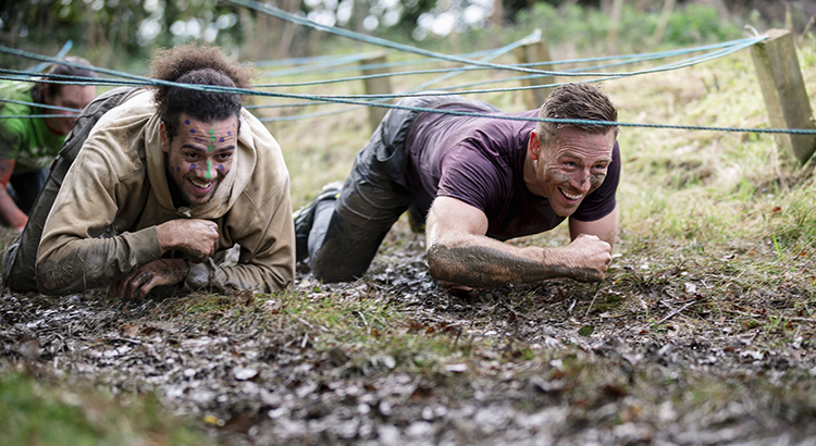Male friends crawling together in mud on outdoor obstacle course