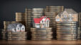 Image depicting miniature model homes resting atop stacks of coins, a metaphor for what goes into home prices in a seller's market
