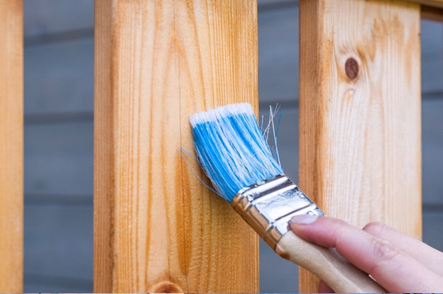 Image depicts a paintbrush running down a wooden board