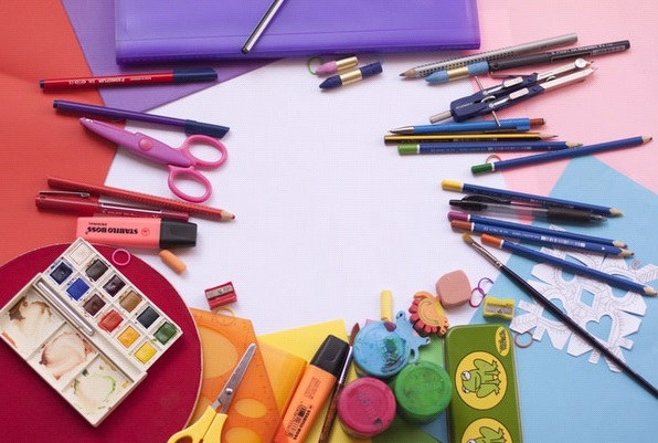 Image depicts a variety of school supplies laid out in colors of the rainbow