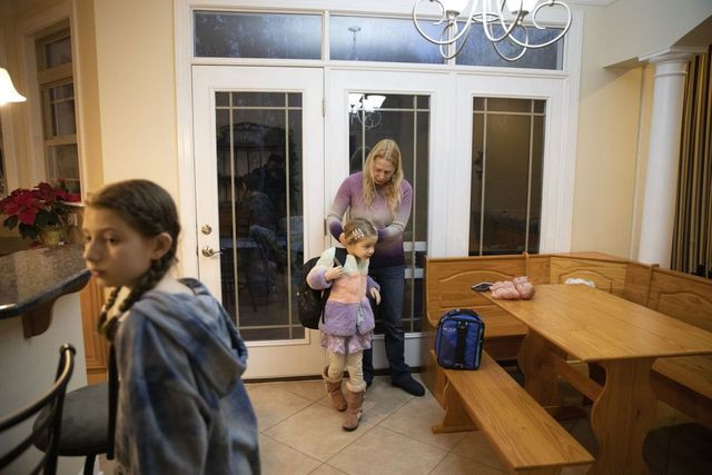 Sara McCauley (back) puts a jacket on her daughter Annaliese McCauley before they head off to school.
