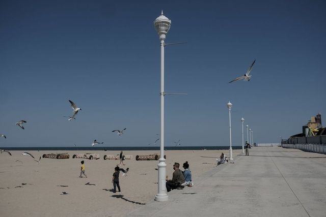 Kids run along the beaches as families distance themselves along the boardwalk on May 13.