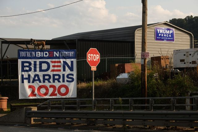 Dueling campaign signs for the Republican and Democratic candidates sit out in Braddock, PA.