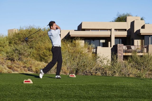 Larry Feldman on one of seven golf courses at Desert Mountain in Scottsdale, Ariz., with his home in the background.