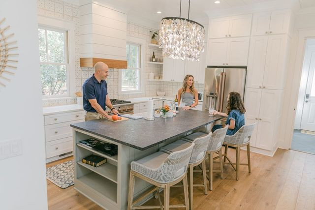 Ryan Malynn, Stephanie Trunzo and their 13-year-old daughter, Adelaide Trunzo Malynn, preparing dinner in the kitchen of the new home they retreated to on Daufuskie Island, S.C. The chandelier is made of locally sourced oyster shells.