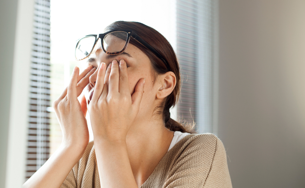 A tired and frustrated women sitting at a desk rubbing her eyes.