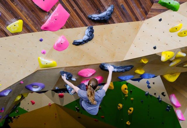 A girl rock climbing in a gym.
