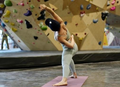 A girl doing yoga in BlocHaven rock climbing gym.