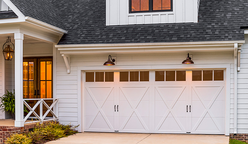 A home who's garage door has been replaced with a custom designed door, increasing home value.
