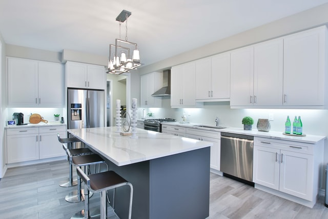 A modern, bright kitchen with an island and white cabinets
