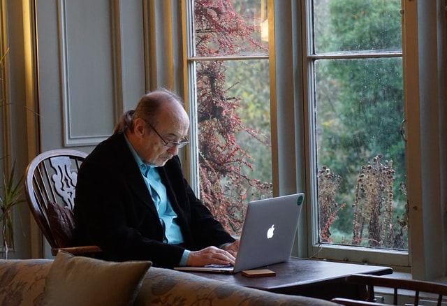 a man typing on his laptop