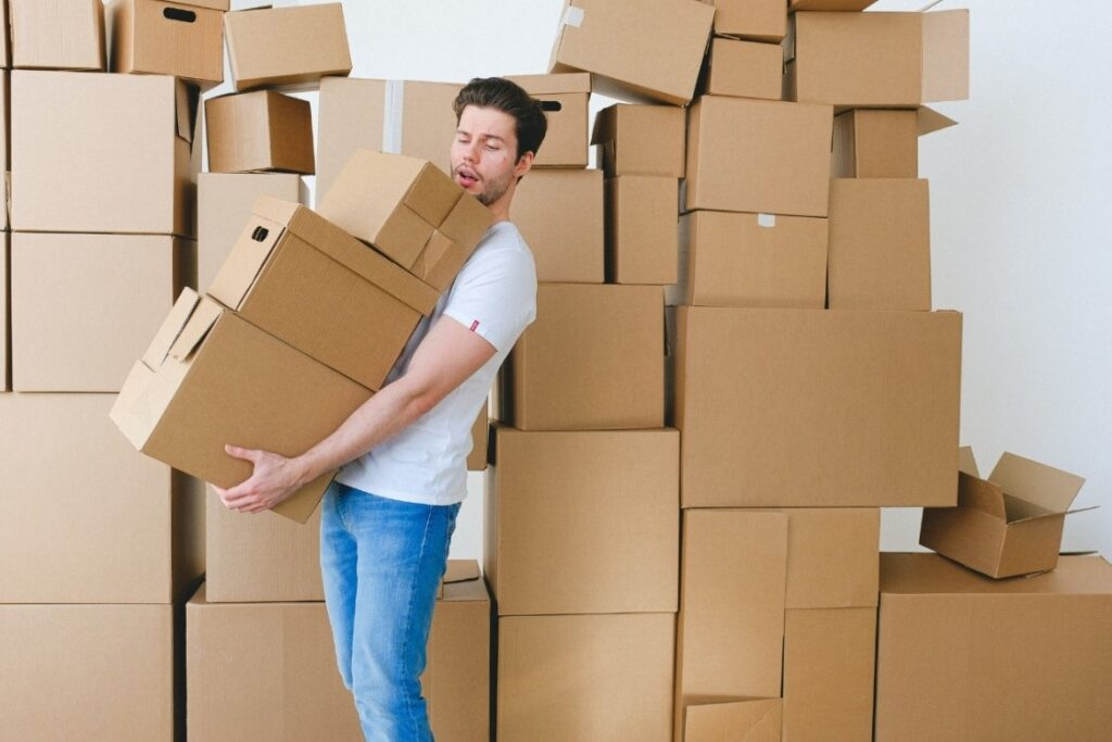 A man carrying a stack of boxes with a big pile of boxes behind him
