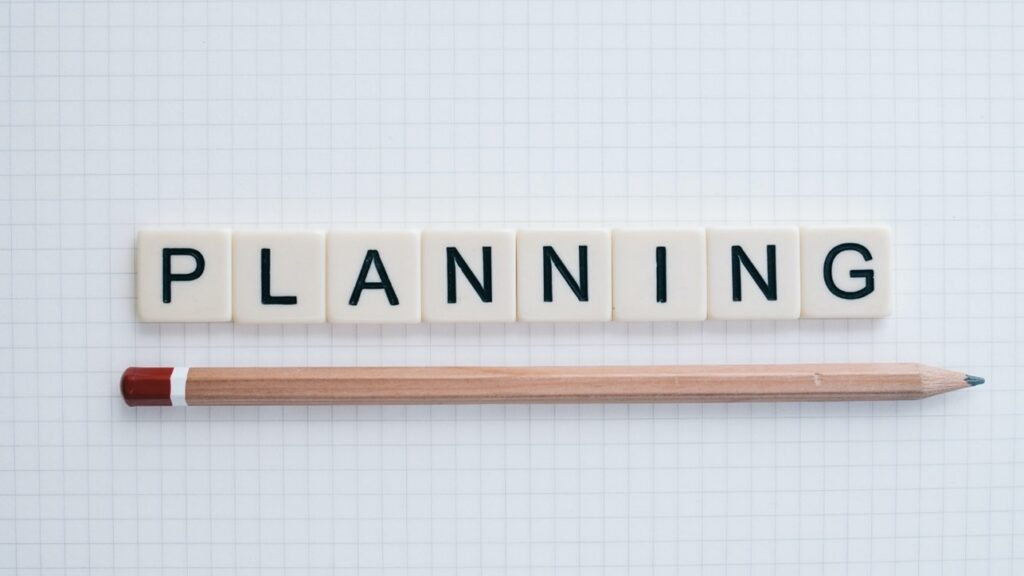 """White scrabble letters forming the word """"planning"""" and a pencil underneath"""