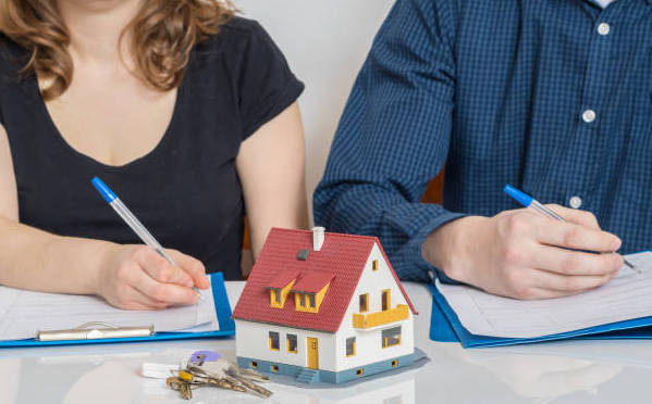 divorced couple signing papers for home sale